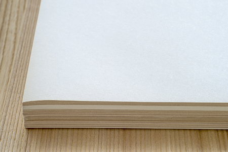 A stack of sheets of clean paper lies on the surface of the table with a natural texture of wood. Background.