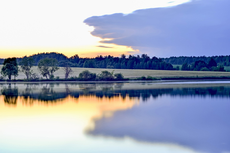 Twilight with reflection of the evening sky in water of the lake tightened by a big cloud. Background.