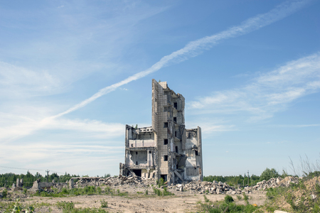 The destroyed big building under demolition against the textured blue sky with white clouds and a trace of the flying plane. Background.