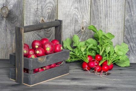 Red radish in a wooden box on the background of a bunch of radish with green tops on a wooden background. The concept of sustainability of the farm product. Stock Photo