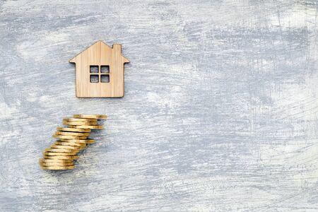 Das Haussymbol besteht aus Bambus und gelb glänzenden Münzen auf einem zerkratzten betongrauen Hintergrund. Das Konzept des Angebots zum Kauf von Immobilien und Finanzanlagen. Platz für Text.