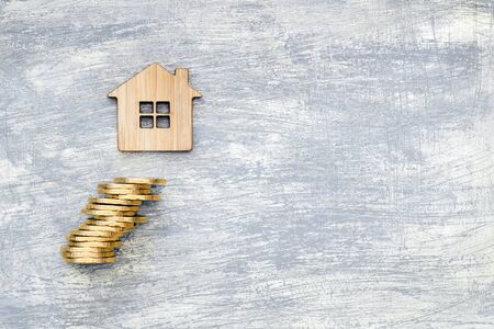The house symbol is made of bamboo and yellow shiny coins on a scratched concrete gray background. The concept of the offer of purchase of real estate and financial investments. Place for text. 写真素材 - 125420876