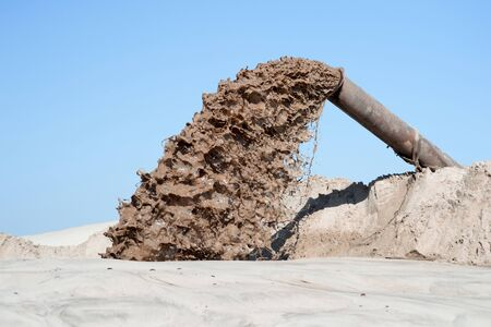 The flow of brown liquid from the pipe on the background of a pile of sand and blue clear sky. The concept of the impact of industrial production on the natural ecosystem.