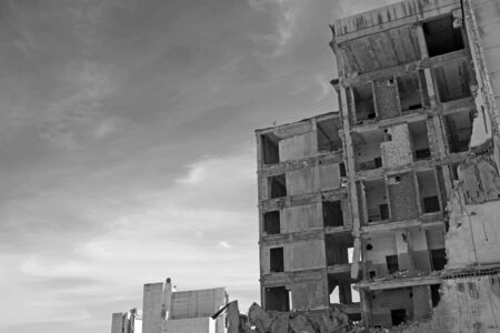 The remains of a destroyed concrete building against the sky. Space for text. Black and white. Background.