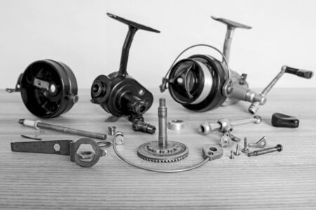 A fishing spinning reel as a whole and a second similar completely disassembled. Preparation for the fishing season: prevention and application of lubrication. Black and white image