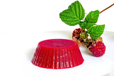 Raspberry jelly on a white plate with raspberry berries on a twig on a white background