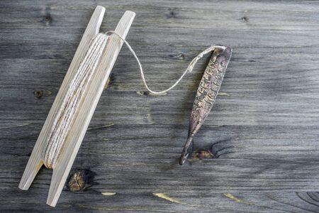 Un attirail ancien pour poissons prédateurs clignotants verticaux. Spinner forgé en cuivre et bobine avec corde sur fond rustique en bois.