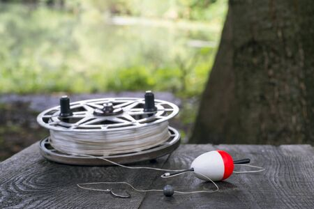 Fishing reel with fishing line, red and white float, hook and sinker on wooden table on natural background. The concept of classic fishing tackle. Text space. 스톡 콘텐츠