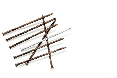 Metal shiny sharp nail in the center of a pile of old rusty nails isolated on white background.