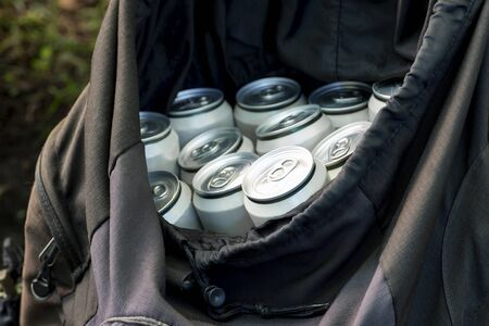 Beer in closed aluminum cans in a black tourist backpack on a natural background. The concept of an integral attribute of picnic and lifestyle on vacation. Banco de Imagens