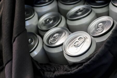 Beer in closed aluminum cans close-up in a black travel bag. The concept of an integral attribute of picnic and lifestyle on vacation. Banco de Imagens