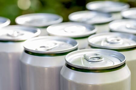 Aluminum closed white cans with beer close-up.