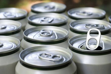 Open close-up of an aluminum can of beer on the background of a group of closed beer cans.