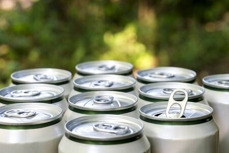 Open close-up of an aluminum can of beer on the background of a group of closed beer cans on a natural background.