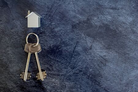 A bunch of keys lie on a vintage dark background along with an imitation of the house in the form of a metal layout. The concept of the offer of sale of real estate. Copy space. Stok Fotoğraf - 129753596