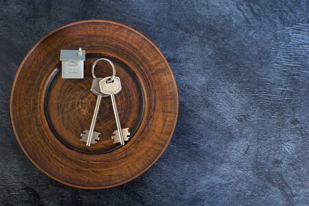 A bunch of keys lie on a vintage plate, along with an imitation of the house in the form of a metal layout. The concept of the offer of sale of real estate. Copy space. Stok Fotoğraf - 129753597