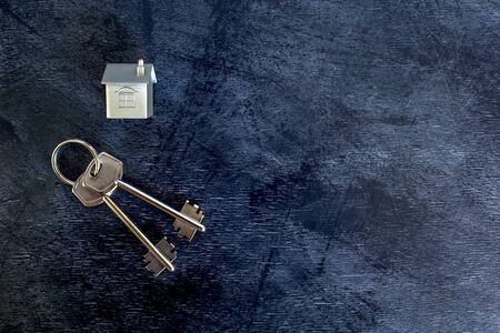 A bunch of keys lie on a vintage dark background along with an imitation of the house in the form of a metal layout. The concept of the offer of sale of real estate. Copy space. Stok Fotoğraf - 129753601