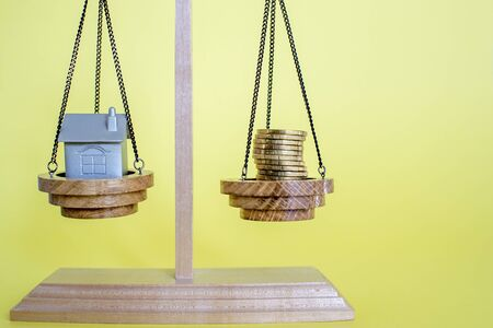 Scales with imitation of the house in the form of a metal keychain and coins on a yellow background. The concept of saving money to buy a house. Copy space.