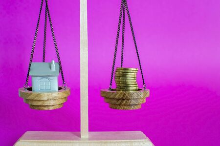 Scales with imitation of the house in the form of a metal keychain and coins on a pink background with a purple hue. The concept of saving money to buy a house. Copy space. Stok Fotoğraf - 129753600