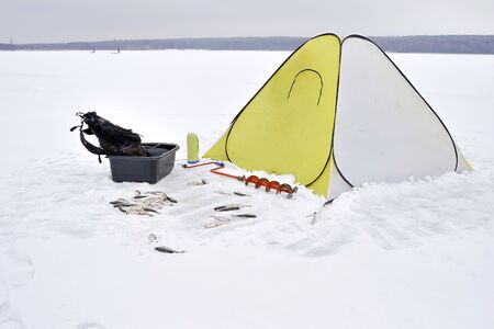 Winter yellow fishing tent fixed on the ice with all the necessary attributes for fishing. Catch roach lying in the snow in front of the tent.