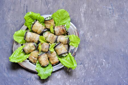 Rolls on green salad leaves of fried eggplant plates stuffed with walnuts, cream, garlic, cheese and cilantro greens.