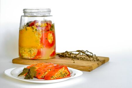 A sliced, vegetable-stuffed red pepper sits on a white plate in close-up against an open can of peppers on a cutting Board with a branch of tarragon. White background, copy space.