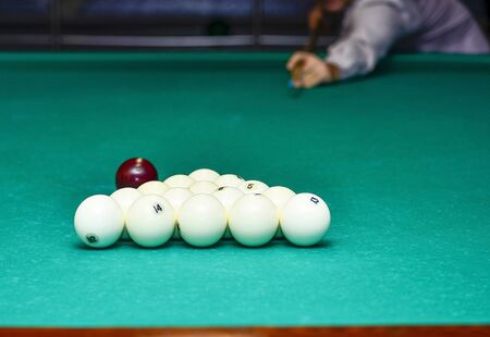 The beginning of the billiard party. The moment the ball hits the pyramid on the background of the player.