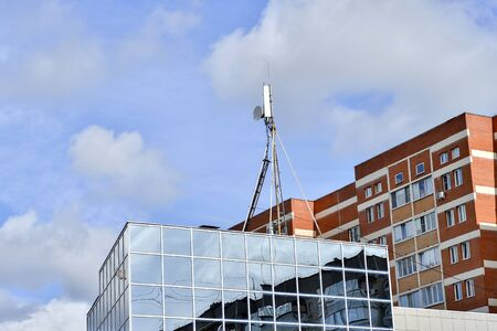 Antennas on a metal support on the roof of a modern building on the background of residential buildings and blue sky.