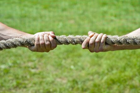 Two men's hands pull the rope each in his own direction. Фото со стока
