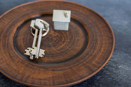 A bunch of keys lie on a vintage plate, along with an imitation of the house in the form of a metal layout. The concept of the offer of sale of real estate.