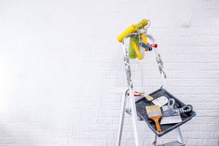 Painted stepladder with black tray, paint bucket, set of brushes and multi-colored spatulas for repair in the form of an abstract art easel shape. The concept of creative approach to interior design. Imagens