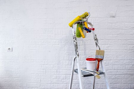Painted metal stepladder with a bucket of paint, a set of colorful rollers and brushes on the background of a white wall decorated with bricks. Imagens