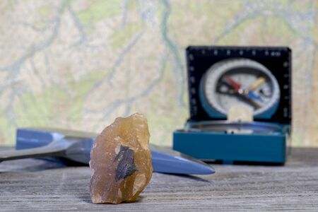 A geologist's hammer, a compass, and a mineral interspersed with iron ore are laid out on a wooden table against a topographic map.