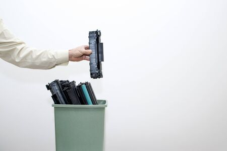Male hand office worker puts in a bucket of spent cartridges. Background.