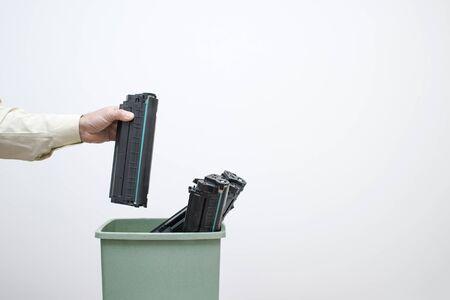 Un employé de bureau masculin met dans un seau de cartouches usagées.