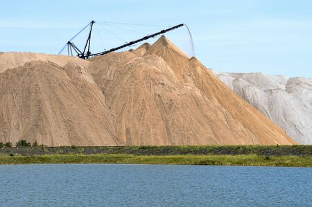 The salt-mine in the form of a hill with conveyor rocks. The foreground is an artificial pond.