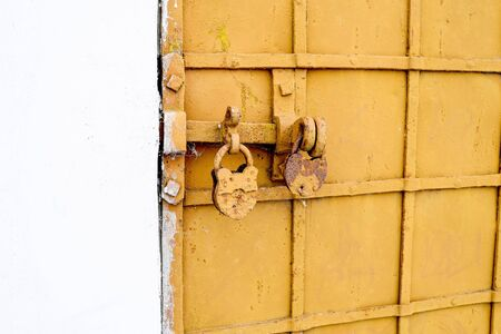 Lock with the bolt closed on the background of the antique-bound door. Background
