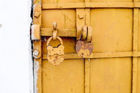 Lock with the bolt closed on the background of the antique-bound door.