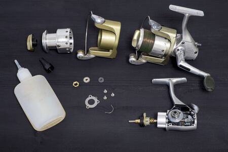 A fishing spinning reel as a whole and a second similar completely disassembled. Preparation for the fishing season: prevention and application of lubrication.