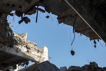 Destruction of buildings. A huge gap in the concrete slab with concrete fragments hanging on the rebar against the blue sky. Background. Space for text. Stock Photo