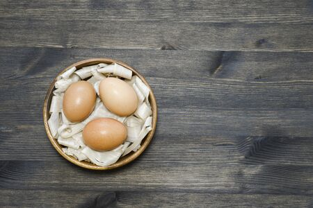 Three chicken eggs on soft wooden shavings in a wooden bowl on a dark wooden table. Background. The concept of healthy farm egg production and careful attitude. Flat lay.