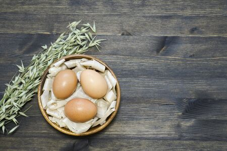 Three chicken eggs on soft wooden shavings in a wooden bowl with ears of oats on a dark wooden table. Background. The concept of healthy farm egg production and careful attitude. Imagens