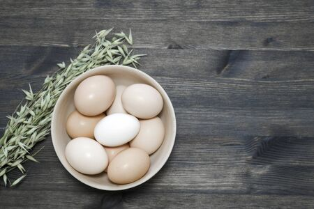 Chicken eggs in a light wooden bowl with oats on a dark wooden table. Background. The concept of healthy farm egg production.