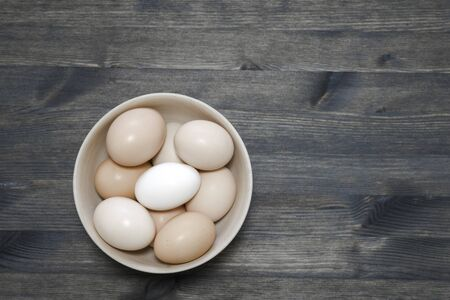 Chicken eggs in a light wooden bowl on a dark wooden table. Background. The concept of healthy farm egg production. Flat lay. Imagens