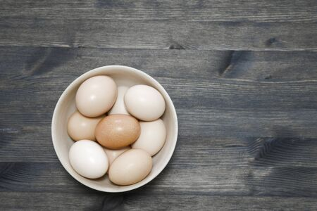 Chicken eggs in a light wooden bowl on a dark wooden table. Background. The concept of healthy farm egg production.