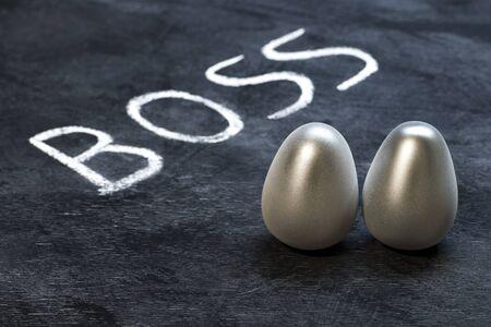 Boss inscription and steel metal eggs on a dark wooden background. Reklamní fotografie