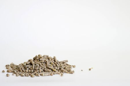 Dry feed pellets are scattered in a pile on a white background. Background.