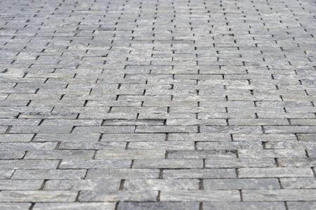 The sidewalk is made of rectangular gray granite bricks . Background.