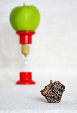 Dried Apple close-up on the background of a green Apple standing on the hourglass. Product life cycle concept under the influence of time.