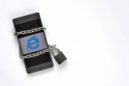 Mobile smart phone in a metal chain on the padlock on white background. The concept of limiting the Internet, as well as the policy of disconnection from the world information resource.